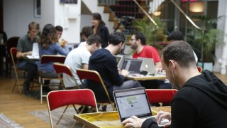 Entrepreneurs work at their computer laptops at the so-called 'incubator' of French high-tech start-ups 'TheFamily' in Paris