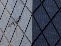 Workers clean windows of a building at a commercial district in Beijing