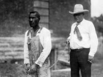Sherrif führt farbigen Gefangenen an einer Kette, 1933