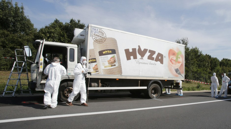 Forensic police officers inspect a parked truck in which up to 50 migrants were found dead on a motorway near Parndorf