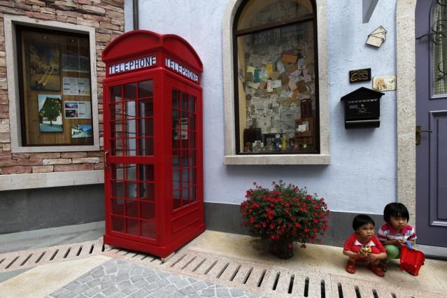 Children pose for pictures at the replica of Austria's UNESCO heritage site, Hallstatt village, in Huizhou
