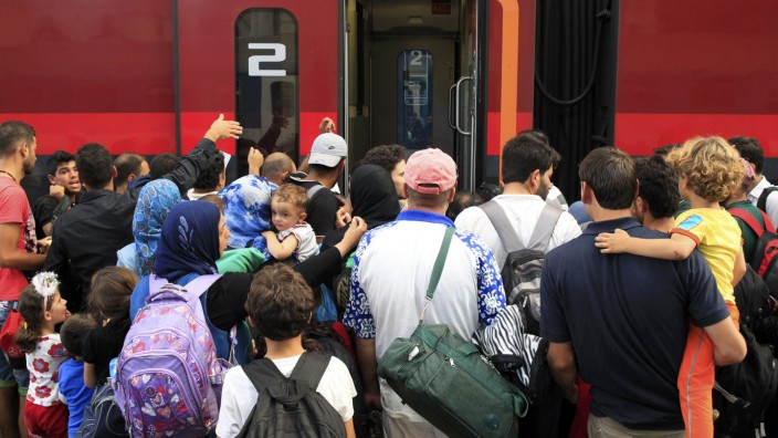 Travellers try to board a train to Austria at the railway station in Budapest