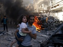 A man carries a girl reacting at a site hit by what activists said were airstrikes by forces loyal to Syria's President Bashar al-Assad on a market place in the Douma neighborhood of Damascus, Syria
