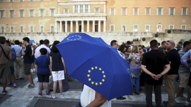A pro-Euro protester holds an umbrella with the European Union symbol during a rally in front of the parliament building in Athens
