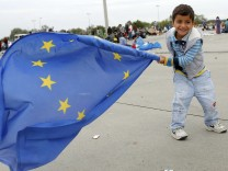A young migrant child plays with a European Union flag after crossing the Austrian border in Nickelsdorf