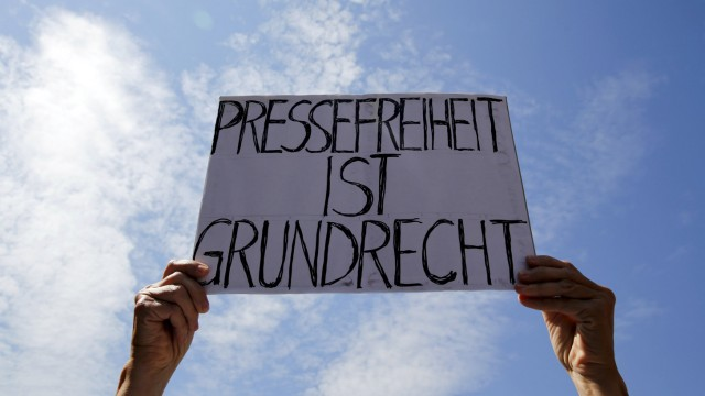 A demonstrator holds up an banner which reads 'The freedom of press is a fundamental right' during a rally to protest against a criminal complaint by the domestic intelligence agency, the Office for the Protection of the Constitution, in Berlin