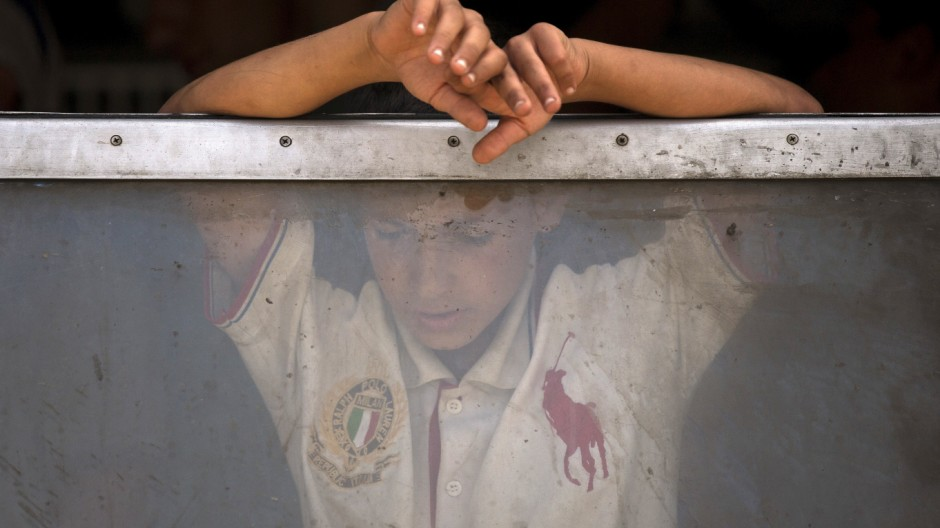 A migrant boy looks through a train window after crossing the Macedonian-Greek border near Gevgelija