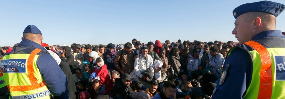 Migrants wait for buses behind police at collection point in Roszke