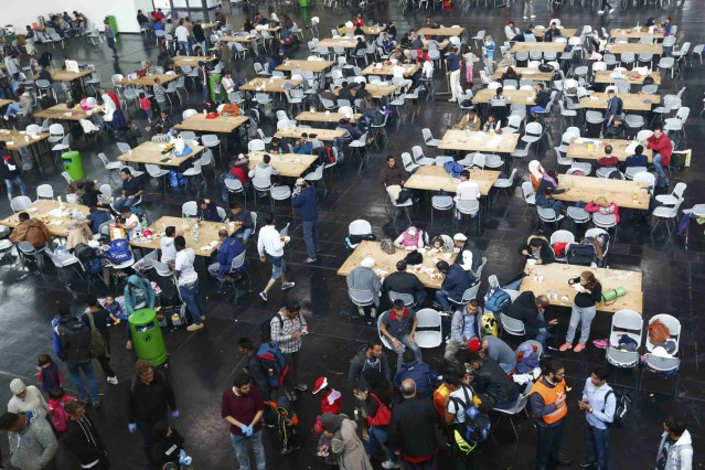 Migrants eat at a makeshift mensa at the fair ground of Munich