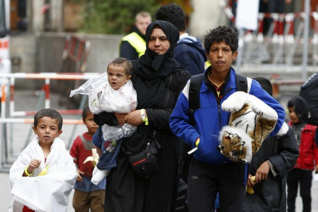 Migrants makes their way to wait for buses after arriving by train at main station in Munich