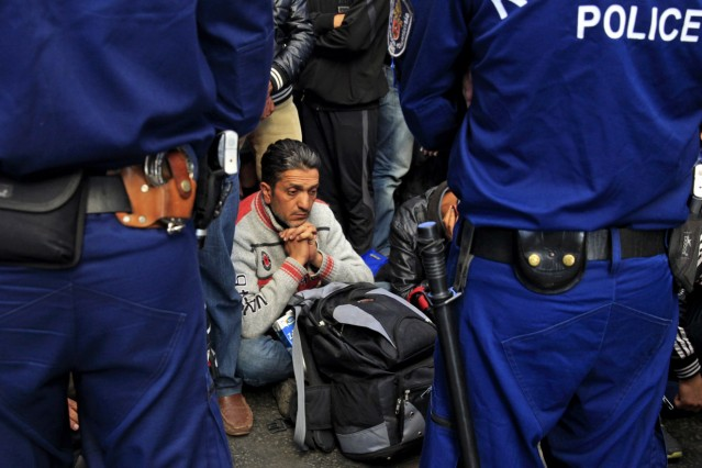 A migrant sits next to his belongings as he waits for train at Keleti railway station in Budapest