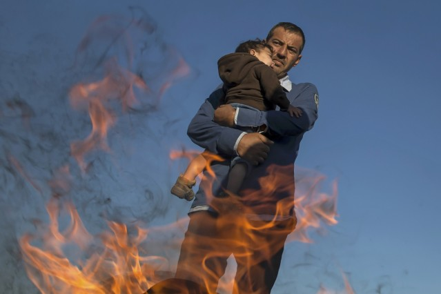 A migrant holds a child as they warm themselves by the fire in a makeshift camp at a collection point in the village of Roszke