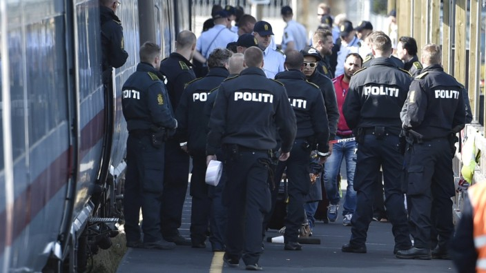 Danish police guard a train carrying migrants, mainly from Syria and Iraq, at Rodby train station, south of Denmark