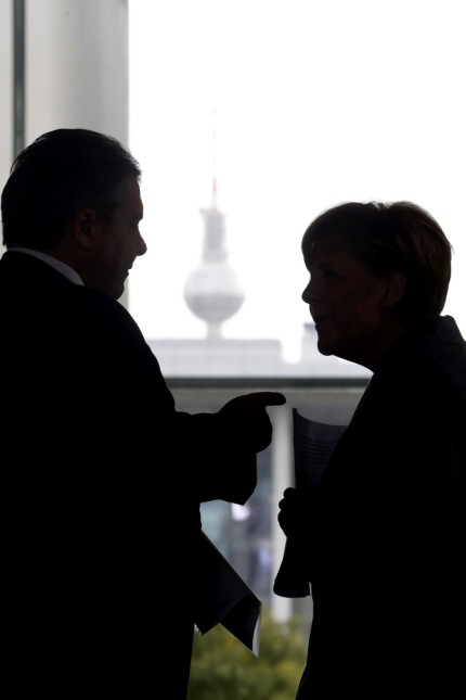 Economy Minster Gabriel gestures as he talks to German Chancellor Merkel after a press conference at the Chancellery in Berlin