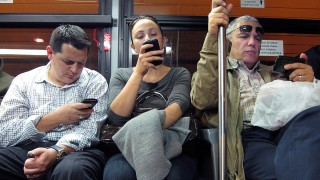 Commuters use their smartphones as they ride in a bus leaving Manhattan through the Lincoln Tunnel in New York