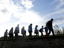 Migrants walk along rail tracks to a makeshift camp at a collection point in the village of Roszke