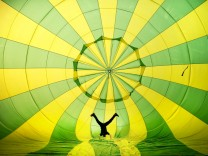 A PILOT PERFORMS A HAND STAND INSIDE A HOT AIR BALLOON AT BRISTOL BALLOON FESTIVAL.