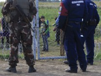 A migrant child looks at Hungarian policemen and soldier in Roszke