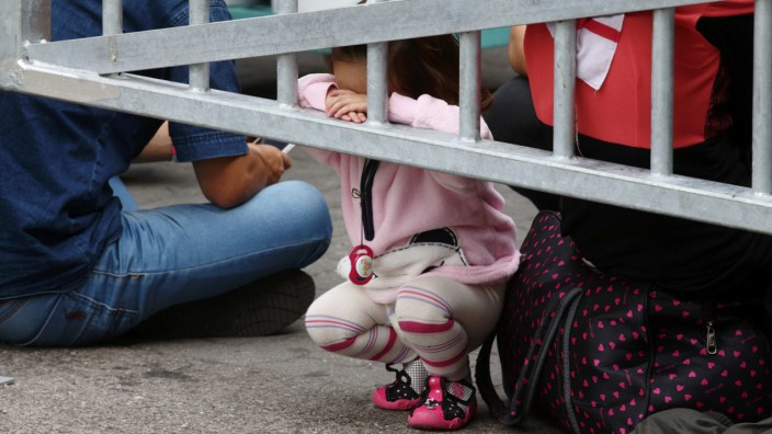 A migrants' child leans to a fencing as they wait for trains at Westbahnhof railway station in Vienna