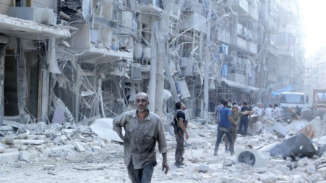 Residents look for survivors in a damaged site after what activists said was a barrel bomb dropped by forces loyal to Syria's president Bashar Al-Assad in Al-Shaar neighbourhood of Aleppo, Syria