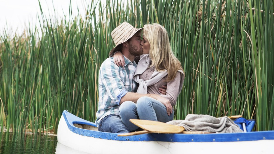Young couple kissing in a canoe on a lake hiding behind straw hat model released Symbolfoto property