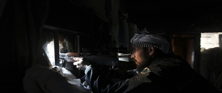 A Free Syrian Army fighter sits in shooting position in Deir al-Zor, eastern Syria
