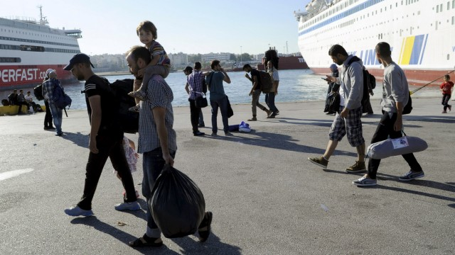 Refugees and migrants walk towards a bus following their arrival onboard the Eleftherios Venizelos passenger ship at the port of Piraeus, near Athens