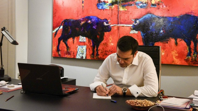 Leftist Syriza party leader and winner of the Greek general elections Tsipras writes down notes at this office at the party's headquarters in this handout photo released by the Syriza press office in Athens