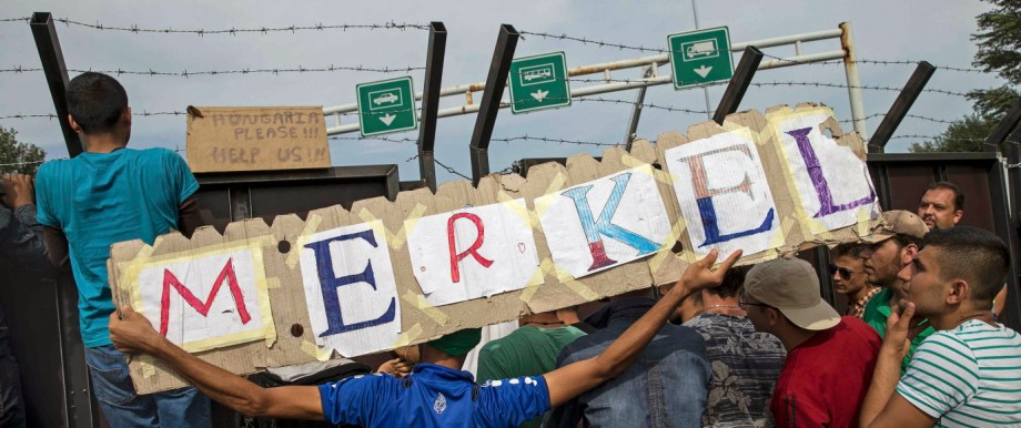 Migrants hold a banner reading 'Merkel' in front of a barrier at the border with Hungary near the village of Horgos