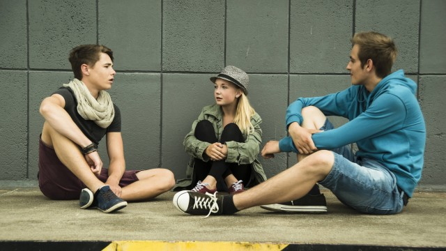Three teenage friends sitting outdoors model released Symbolfoto PUBLICATIONxINxGERxSUIxAUTxHUNxONLY