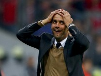 Bayern Munich's coach Guardiola reacts after his team scored a goal during their German first division Bundesliga soccer match against Wolfsburg in Munich