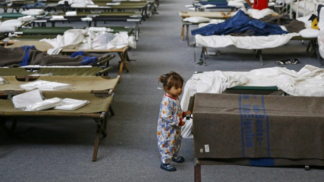 A migrant child stands next to a bed at an improvised temporary shelter in a sports hall in Hanau