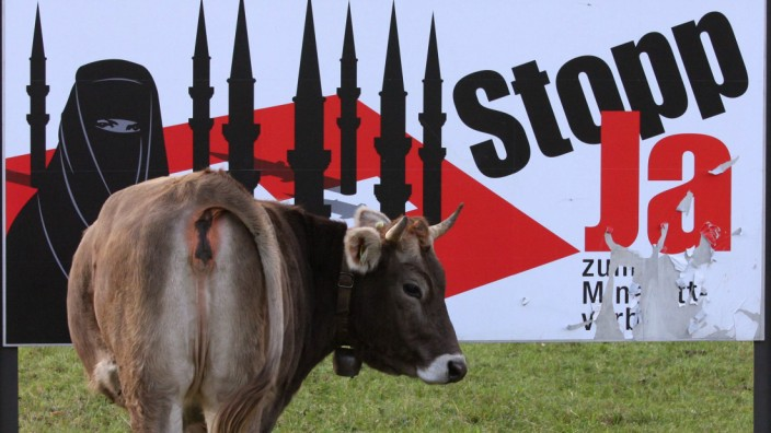 A cow stands in a meadow next to a display advertising the initiative against the construction of new minarets in