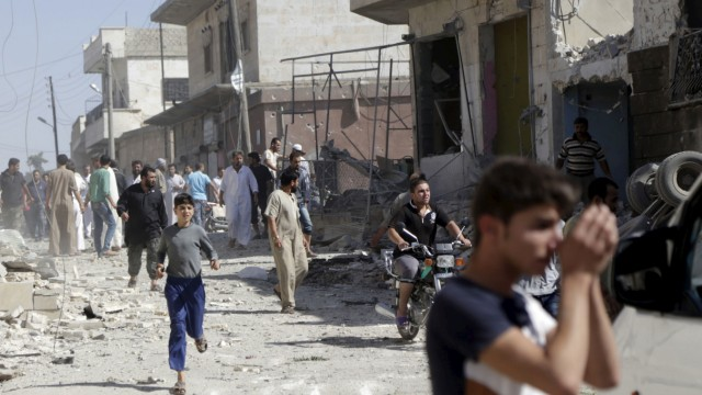 People gather at a site hit by what activists said was an airstrike by forces loyal to Syria's President Bashar al-Assad, in Talmenes village in the southern countryside of Idlib