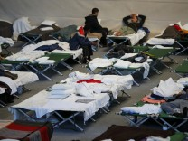 Migrants rest at temporary shelter in a sports hall in Hanau