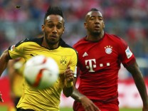 Borussia Dortmund's Aubameyang challenges Bayern Munich's Boateng during their German first division Bundesliga soccer match in Munich