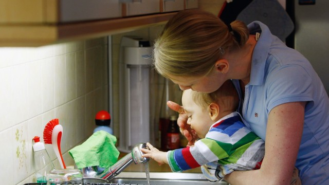 Leonard (ten-month-old) gets his mouth cleaned by mother Veronika Rixom in kitchen in Ismaning