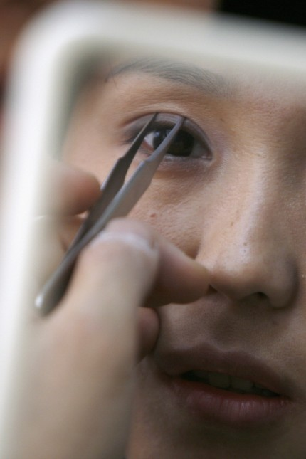 Korean plastic surgeon Kim demonstrates the so-called 'double eyelid surgery' for a patient during a consulting session in his clinic in Shanghai