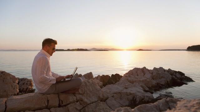 Croatia Zadar Young man using laptop on beach model released PUBLICATIONxINxGERxSUIxAUTxHUNxONLY H
