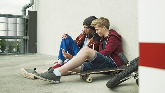 Two boys sitting on ground looking at cell phone model released PUBLICATIONxINxGERxSUIxAUTxHUNxONLY
