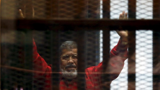 Deposed President Mohamed Mursi greets his lawyers and people from behind bars at a court wearing the red uniform of a prisoner sentenced to death, during his court appearance with Muslim Brotherhood members on the outskirts of Cairo, Egypt