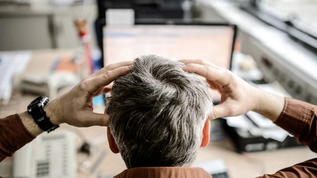 Ein Angestellter sitzt in einem Büro vor seinem Computer und rauft sich die Haare