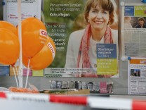 Balloons of German Chancellor Merkel's CDU are seen in front of an election campaign poster of mayor candidate Reker in Cologne