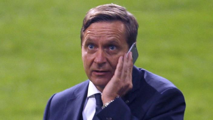 Schalke 04's manager Heldt listens at his mobile phone after the Bundesliga first division soccer match against Hertha Berlin in Gelsenkirchen
