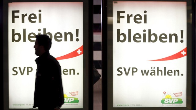 A man walks past election campaign posters of the Swiss People's Party at the main train station in Zurich