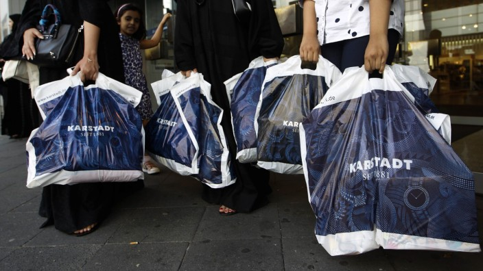 Women carry bags from the German department store chain Karstadt in Duesseldorf