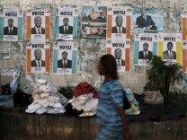 Woman walks past campaign posters ahead of the October 25 presidential election, in Abidjan
