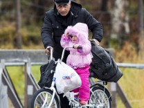 Man pushes a girl across the border from Russia to Norway on a bicycle with flat tyres at the Storskog border station in northern Norway