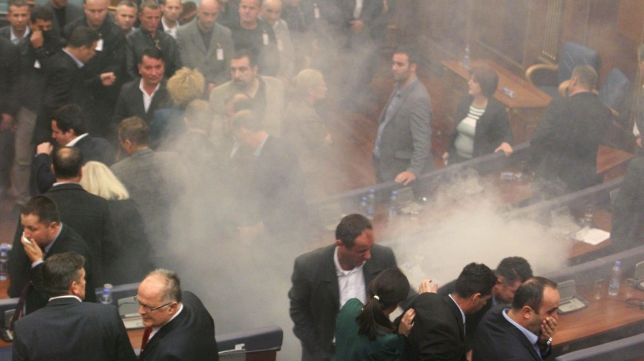 Lawmakers react after opposition politicians release tear gas in parliament in Pristina