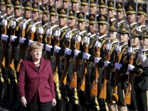 Germany's Chancellor Angela Merkel inspects honour guards during a welcoming ceremony in Beijing